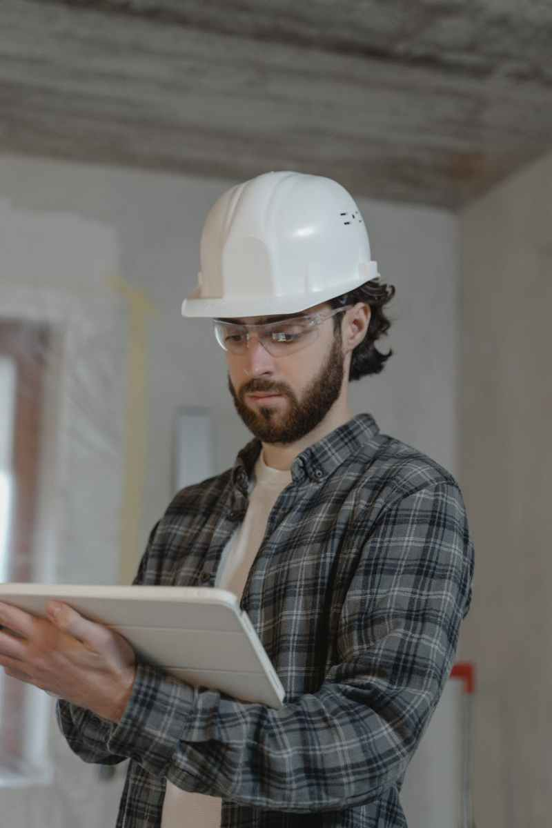 man in black and white plaid button up shirt wearing white hard hat