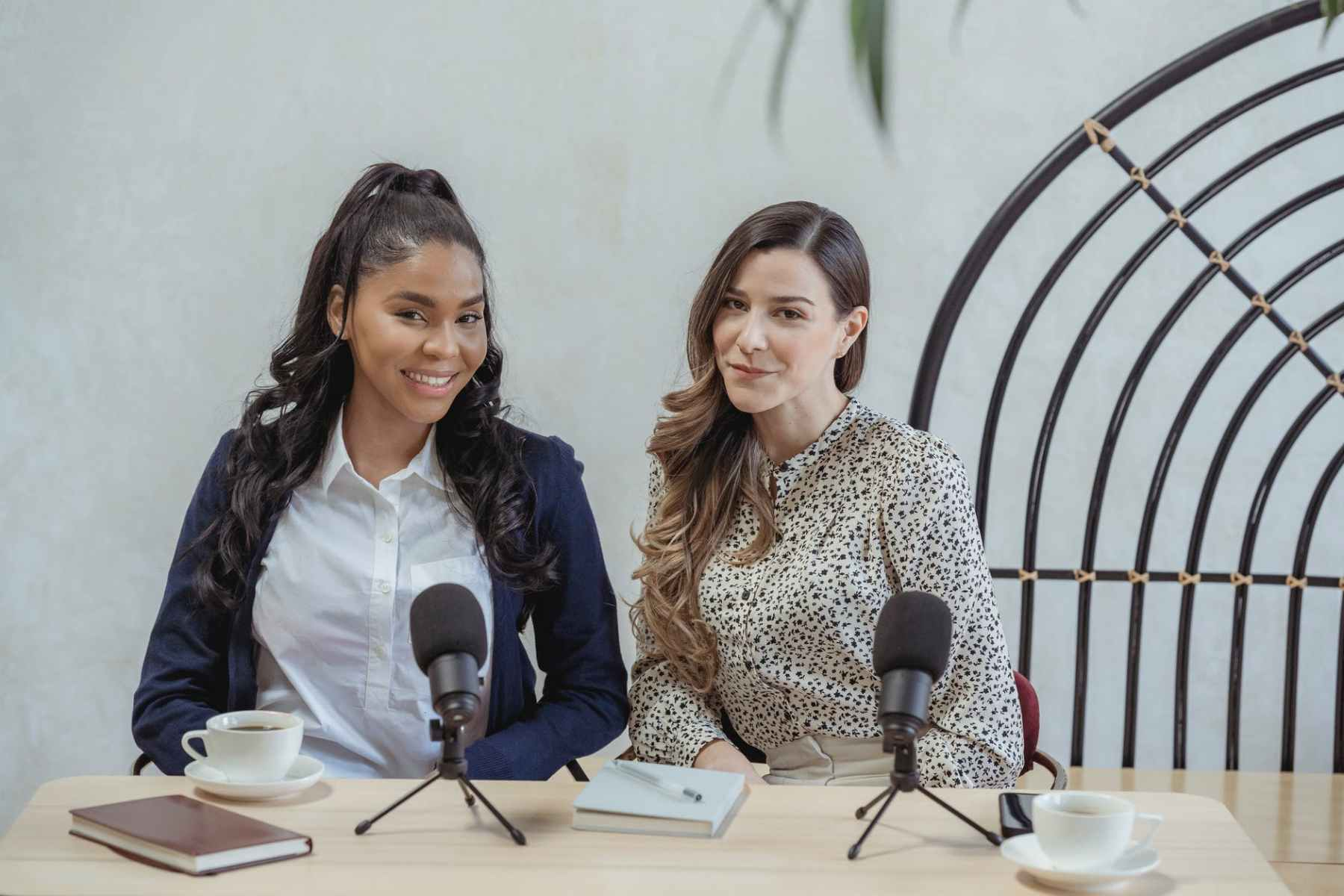 content young diverse businesswomen sitting at table with microphones during meeting