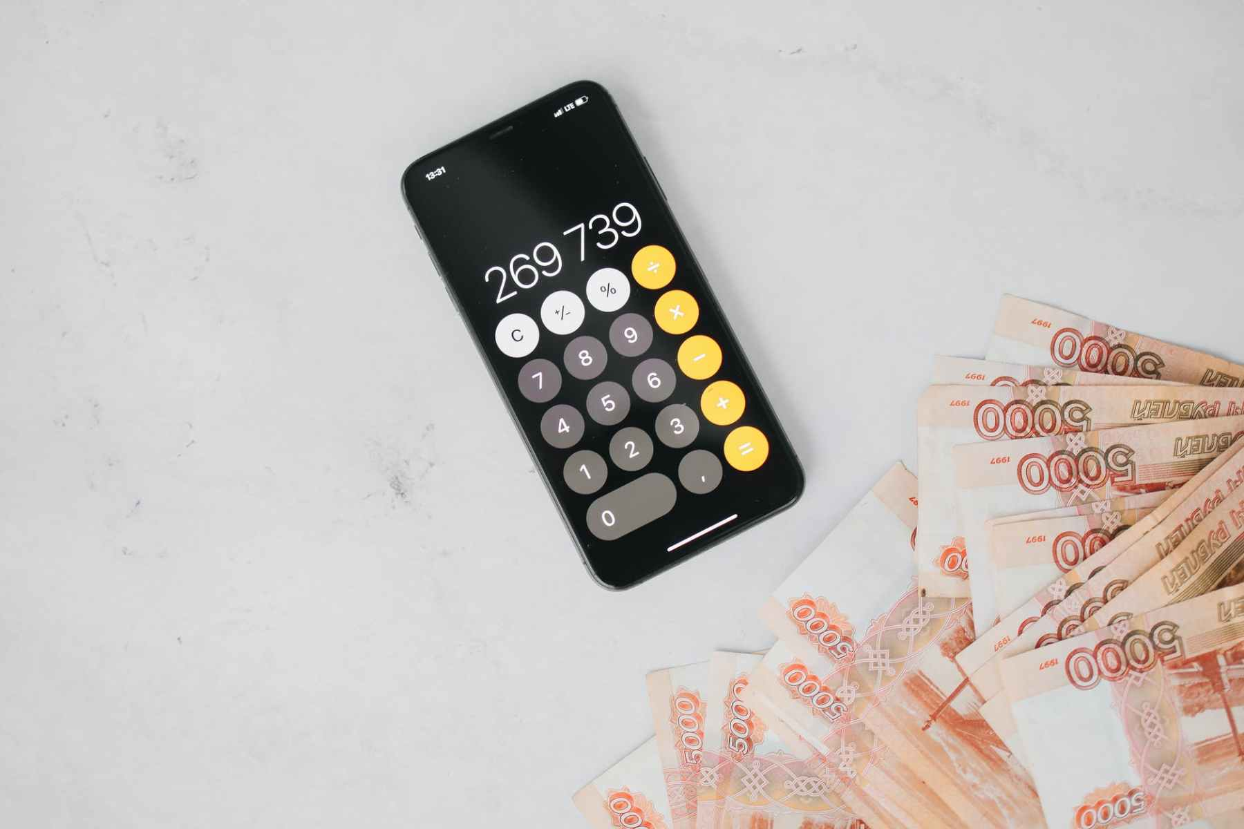 a cellphone calculator and cash on a flat surface